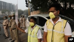 Volunteers and policemen wear pollution masks and stand at a busy crossing with the banner saying obey odd and even, remove pollution, in New Delhi, India, Monday, Nov. 4, 2019. (AP Photo/Manish Swarup)
