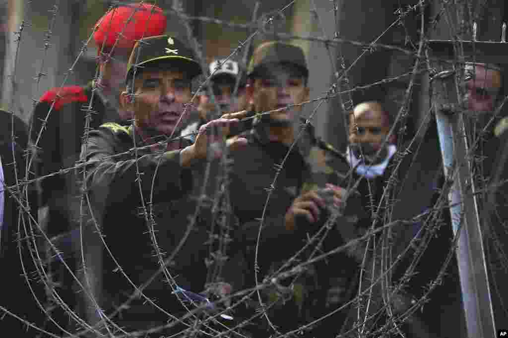 An Egyptian officer, left, attempts to talk to protesters behind a newly erected barbed wire barricade by the Egyptian army near Tahrir square in Cairo, November 24, 2011. (AP)