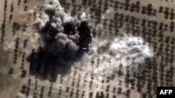 FILE - An image taken from video footage made available on the Russian Defense Ministry's official website purports to show an explosion after airstrikes carried out by Russian air force on what Moscow says was an Islamic State facility in the Syrian province of Idlib, Oct. 15, 2015.