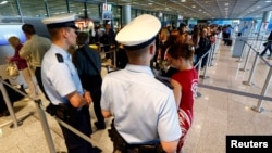 FILE - Police officers are seen patrolling at a security gate inside the main terminal of Frankfurt Airport.