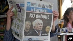 """A woman reads the French newspaper """"Le Parisien"""" headlining on IMF head arrest, in Paris, Tuesday, May 17, 2011"""