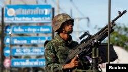 Seorang tentara Thailand memegang senjata mesin di tengah kota Bangkok (20/5). (Reuters/Chaiwat Subprasom)