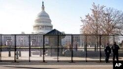 Полиция Капитолия несет дежурство у забора, который установлен перед зданием Конгресса США в Вашингтоне.