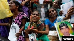 FILE - Tamil women cry as they hold up images of their disappeared family members during the war against Liberation Tigers of Tamil Eelam (LTTE) at a protest in Jaffna north of Colombo, Aug. 27, 2013.