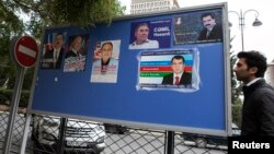 A man passes an election poster with portraits of presidential candidates in central Baku, October 4, 2013.