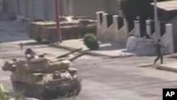 本星期一名士兵在敘利亞哈馬鎮的一輛坦克附近走過