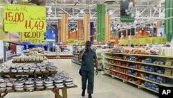 A soldier walks through the Exito hypermarket branch in Valencia, Venezuela, as government officials take over management of the French-owned store, accusing it of price speculation following the country's currency devaluation, Jan 19, 2010 (file photo)