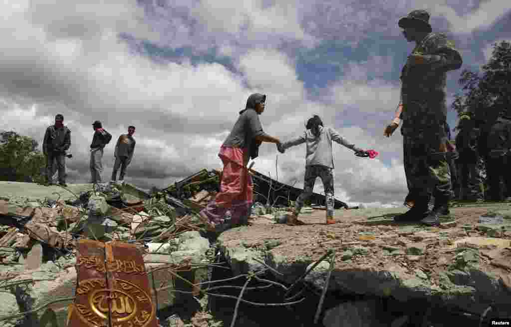 Residents walk on a collapsed mosque in Blang Mancung village after a 6.1 magnitude earthquake hit Aceh province, July 3, 2013.