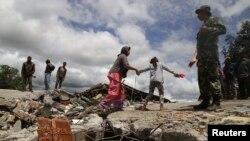 Warga berjalan di antara reruntuhan bangunan masjid yang hancur di desa Blang Mancung pasca gempa berkekuatan 6.2 SR mengguncang provinsi Aceh (3/7).