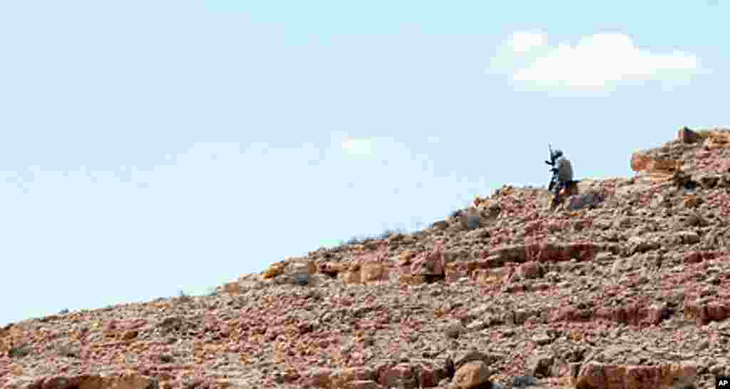 An NTC fighter searches for pro-Gadhafi snipers, Bani Walid, Libya, September 10, 2011. - E. Arrott