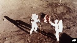 "In this July 20, 1969 file photo, Apollo 11 astronauts Neil Armstrong and Edwin E. ""Buzz"" Aldrin, the first men to land on the moon, plant the U.S. flag on the lunar surface. (NASA)"