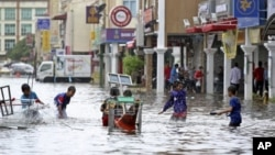 Children play in a flooded street in downtown Kota Bharu, Kelantan, Malaysia.