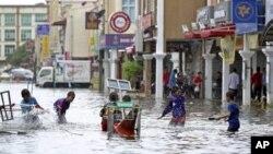 Trẻ em chơi đùa trong một con đường bị ngập nước sau các cơn mưa lớn, ở Kota Bharu, Malaysia 25/12/12