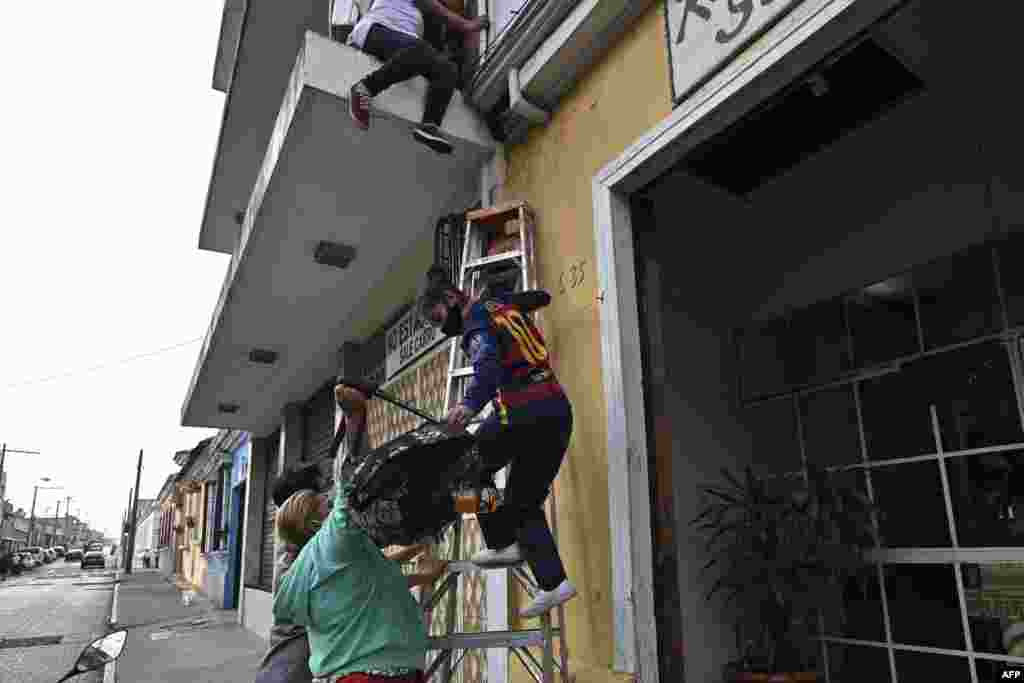 A teenager is helped with a ladder as she climbs down from a building to escape the Zafiro I shelter in Guatemala City, Feb. 17, 2021.