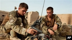 In this undated handout photo from Britain's Ministry of Defense made available on July, 31, 2010, Lt. Olly Field, left and Bombadier Matthew Nichols check their kit, after moving into a compound outside Sayedebad, central Helmand, Afghanistan.