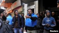 구호물품을 전달하기 위해 시리아 홈스에 도착한 유엔 요원들이 현지인들에 둘러싸여 있다.