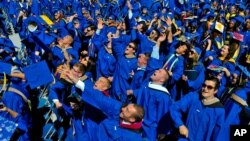 Graduates throw their caps in the air in triumph at the University of Delaware's commencement ceremony in Newark, Del., Saturday, May 31, 2014. (AP Photo/Emily Varisco)