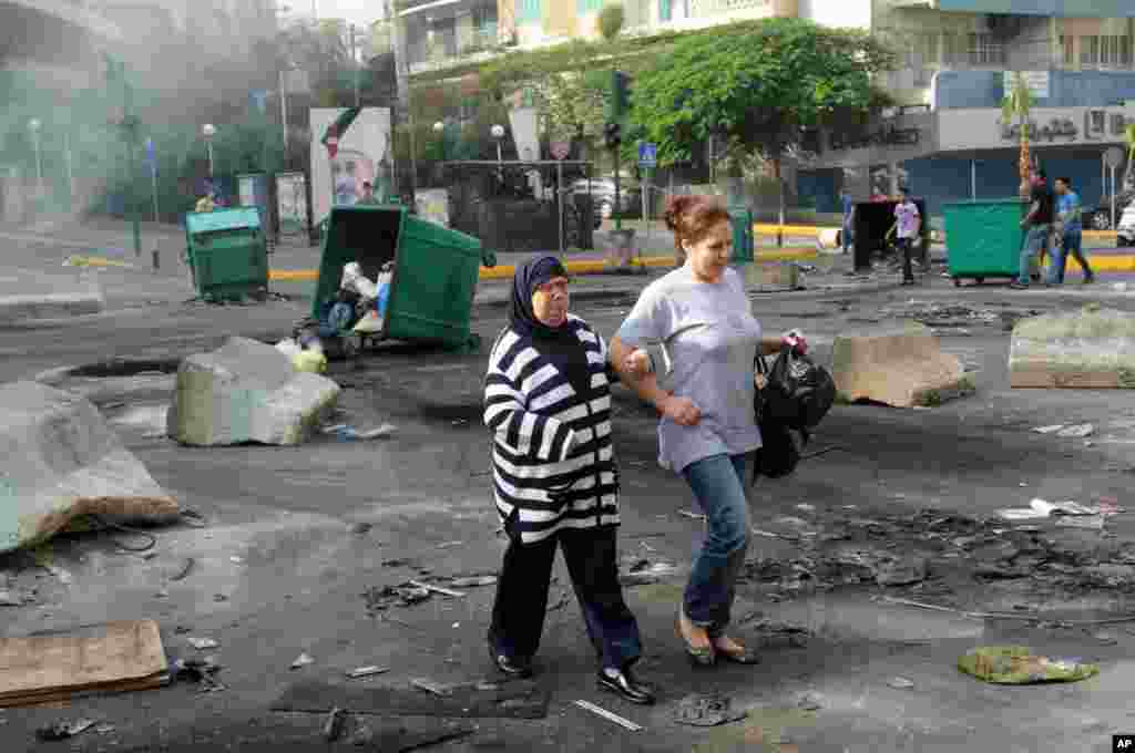 Women walk through a road block of burning garbage containers laid by Sunni protesters angry at the killing of Brig. Gen. Wissam al-Hassan in Beirut, Lebanon, October 20, 2012.