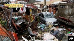 Xe cộ và tử thi nằm giữa đống đổ nát sau bão Haiyan trong thành phố Tacloban, tỉnh Leyte, miền trung Philippines.