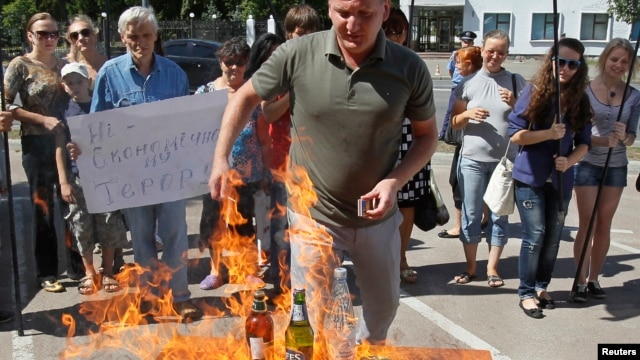 "Members of a Ukrainian activist group burn goods produced in Russia as they hold a rally against what they see as undue Russian trade pressure on Ukraine, in front of Russia's Embassy in Kyiv, August 16, 2013. The sign reads: ""Stop economic terror."