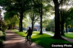A student rides a bicycle across campus at Elon University in Elon, North Carolina.