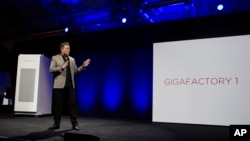 FILE - Elon Musk, CEO of Tesla Motors, unveils the company's Powerpack, in Hawthorne, California, April 30, 2015. A 53-megawatt hour battery station will soon be providing power for the Hawaiian island of Kauai.