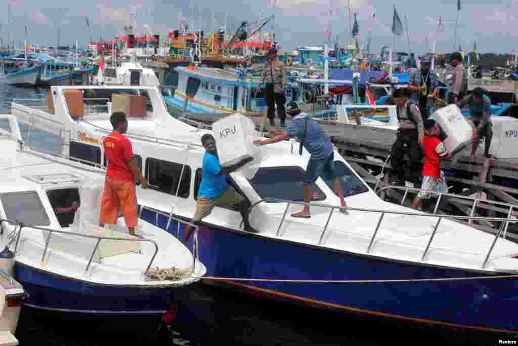 Para pekerja memuat barang-barang keperluan pemilu ke dalam sebuah kapal untuk didistribusikan ke Sorong, Papua Barat, 16 April 2019. (Foto: Antara Foto/Olha Mulalinda/ via REUTERS)