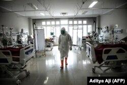 Seorang tenaga medis memeriksa pasien-pasien COVID-19 di unit perawatan intensif (ICU) di sebuah rumah sakit di Bogor, Jawa Barat di tengah lonjakan tingkat infeksi, 18 Juni 2021. (Foto: Aditya Aji/AFP)