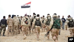 In this photo released by the Syrian official news agency SANA, Syrian soldiers gather around a Syrian national flag in Palmyra, Syria, March 27, 2016.