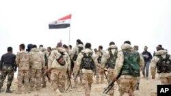 叙利亚官方通讯社发布的照片显示,叙利亚军人聚集在叙利亚国旗旁边(2016年3月27日)