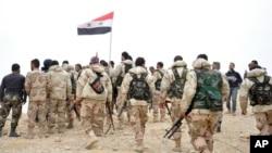 叙利亚官方通讯社发布的照片显示,叙利亚军人聚集在叙利亚国旗旁边。(2016年3月27日)