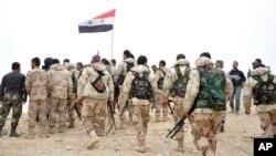 Binh sĩ Syria tập hợp xung quanh một lá cờ quốc gia Syria ở Palmyra, ngày 27/3/2016.