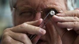 A British diamond dealer inspects a raw diamond on the trading floor of Israel's diamond exchange in Ramat Gan near Tel Aviv, October 30, 2012.