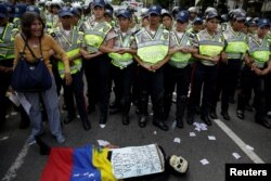 "An opposition supporter wearing a costume lies in front of riot police during a rally' in Caracas, Venezuela, Jan. 23, 2017. The sign reads ""Venezuelans starve. There is no food or medicine."""