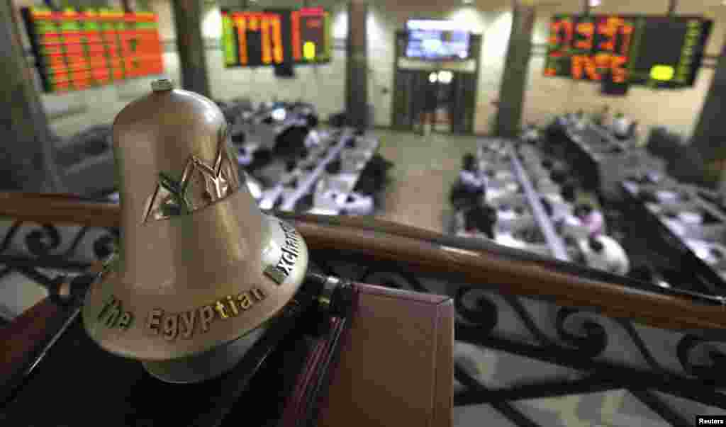 Traders are seen working below the Egyptian Exchange bell at the stock exchange in Cairo. Selling pressure from foreign investors dragged Egypt's bourse down to a near 16-week low on Sunday as the country's economic situation worsens.