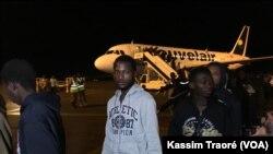 152 Maliens rapatriés de la Libye au pied de l'avion, à l'aéroport Modibo Keita de Bamako Senou, Bamako, Mali, 7 décembre 2017. (VOA/Kassim Traoré)