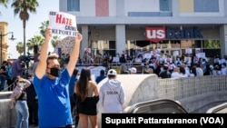 An Asian-American man raises a sign during a rally to speak up and show solidarity for the AAPI community at Thai Town, Los Angeles California, U.S., on April 8, 2021.
