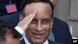 FILE - Pakistan's former ambassador to the U.S., Hussain Haqqani, salutes to media as he leaves after appearing before a judicial commission at a high court in Islamabad, Pakistan, Jan. 9, 2012.