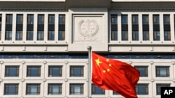 FILE - A Chinese flag billows outside Shandong Province Supreme People's Court in Jinan.