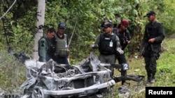 Nhân viên an ninh Thái Lan vây quanh đống đổ nát của một chiếc xe được dùng trong vụ đánh bom ở tỉnh Yala, ngày 10/2/2013.