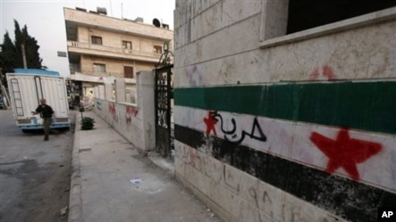 "A wall with the Syrian revolutionary flag and Arabic writing which reads ""freedom,"" northern Syria, June 3, 2012."