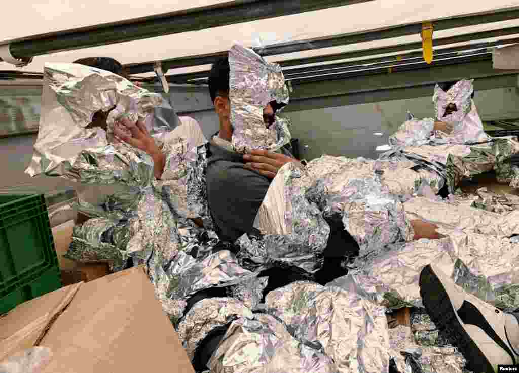 Iraqi refugees wrapped in aluminium foil to hide from an x-ray detector are pictured inside a truck at Pendik Port as they try to reach Italy in Istanbul, Turkey, June 6, 2018.