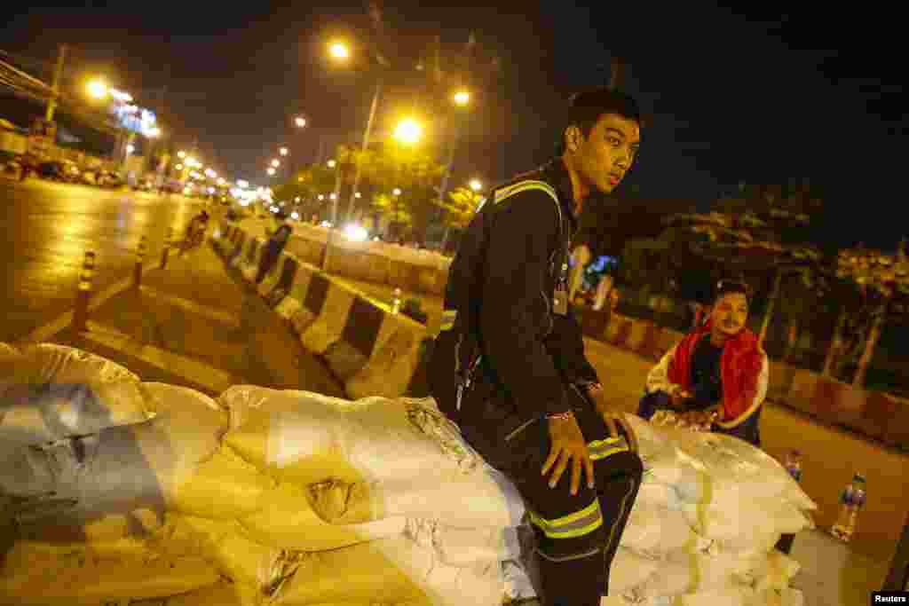 Một nhân viên cứu hộ ngồi trên hàng rào chướng ngại của những người biểu tình chống chính phủ dựng lên chặn một con đường gần khu vực Tòa Nhà Chính phủ 12/1/14