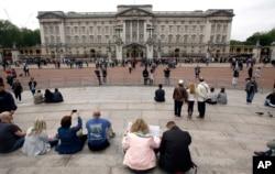FILE - Tourists gather around Buckingham Palace in London, May 19, 2016.