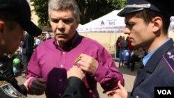 Участник акции «Бессмертный полк» Олег Колесник снимает «георгиевскую лену» по требованию работника полиции