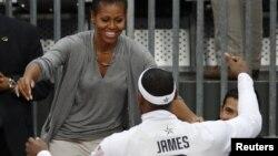 La primera dama de Estados Unidos Michelle Obama abraza a LeBron James al final del juego que los estadounidenses ganaron a Francia, en el baloncesto masculino.