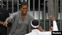 Ibu negara Michelle Obama memeluk pemain bola basket AS, LeBron James setelah memenangkan pertandingan melawan tim Perancis (29/7).