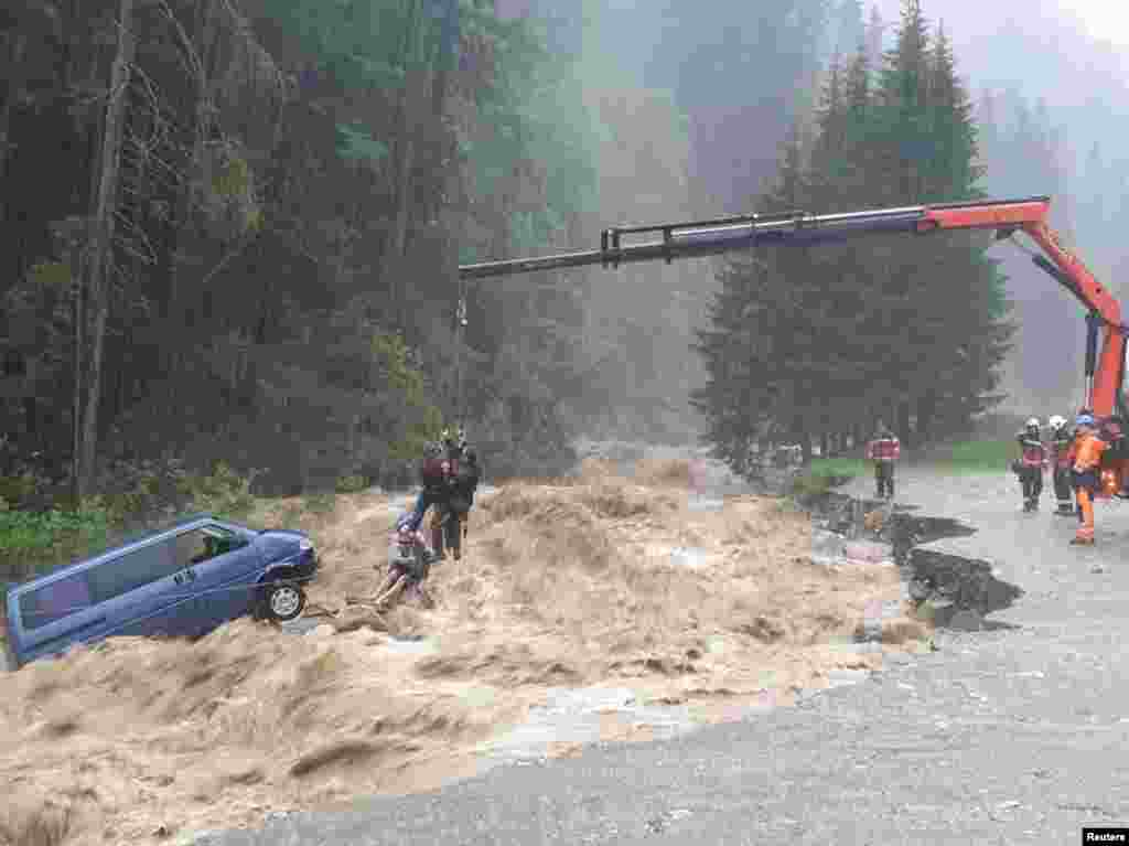 Two occupants of stranded van are lifted unhurt by a crane during heavy rain in this picture released by the Graubuenden Police in Spluegen, Switzerland, June 12, 2019.
