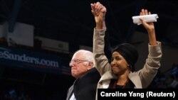 La représentante Ilhan Omar (à droite) tient la main du sénateur Bernie Sanders à l'Université du Minnesota - Minneapolis à Minneapolis, Minnesota, États-Unis le 3 novembre 2019. REUTERS/Caroline Yang
