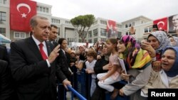 FILE - Turkey's President Tayyip Erdogan (L) greets students and parents during a ceremony to mark the start of the new school year at Ahmet Sani Gezici Girls' Imam Hatip School in Istanbul, Turkey.